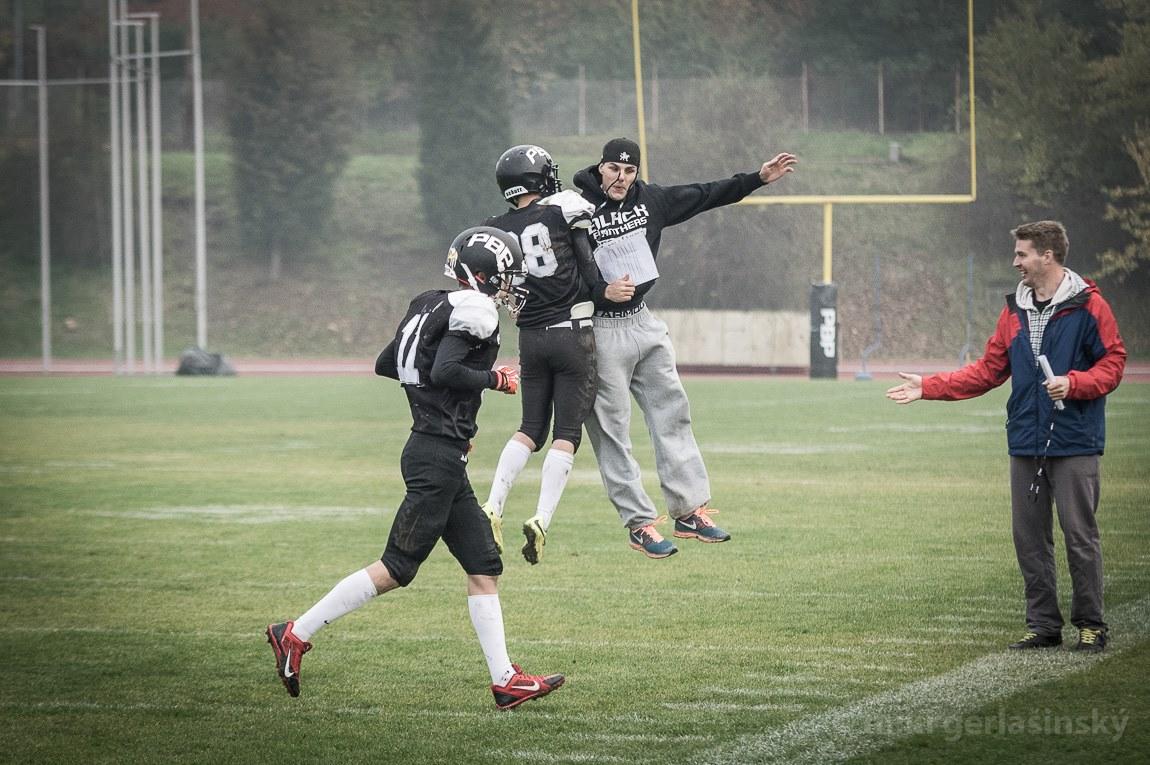 Oslava domácího touchdownu. V popředí zleva Tomáš Hlach a Jan Dundáček, za nimi ve výskoku skórující Honza Tesař a jmenovec Honza Štiegler v pozici trenéra. Foto: Miki Gerlašinský