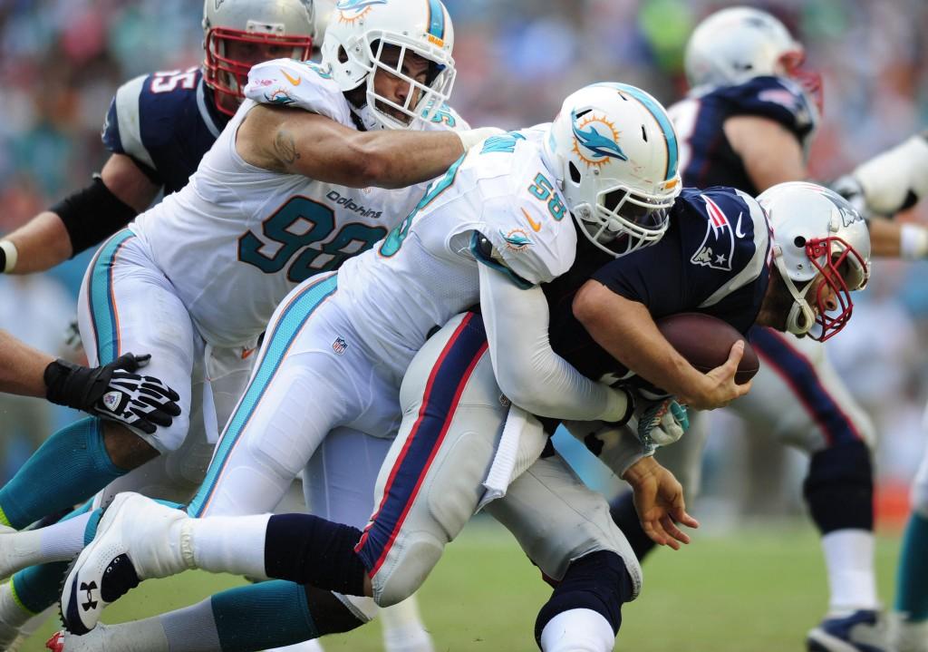 Chris McCain z Miami Dolphins sackuje Toma Bradyho ve čtvrté čtvrtině úvodního zápasu sezóny 2014/2015.